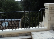 Wrought iron external balustrade with scroll panel and urn finial detail