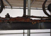 Rust jacking and decay where the original overthrow is fixed to the modern support beam.