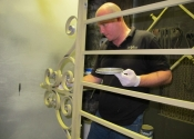 Ironart's Dean Conway applying paint system to the St Mary Tory gates