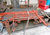 The brackets laid out on the workshop bench. Red oxide paint has been used
