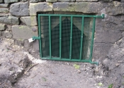 Padlocked security grille for a drain in a private garden. Finished in Mid Brunswick Green