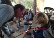 Robert Smith shows his junior assistant how to heat and hammer on the forge