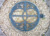 Decorative wrought iron well cover mounted on wood by Ironart of Bath