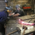 Shaping the red hot metal around the 'former'